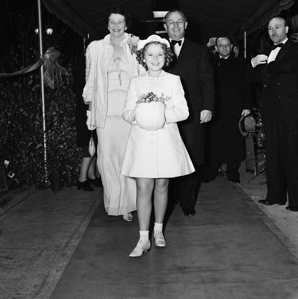 """<p>In 1936, Fox resigned Shirley for another seven-year contract, bumping her pay up to <a href=""""https://www.history.com/this-day-in-history/shirley-temple-receives-50000-per-film"""" rel=""""nofollow noopener"""" target=""""_blank"""" data-ylk=""""slk:$50,000 per film"""" class=""""link rapid-noclick-resp"""">$50,000 per film</a> — an unheard of amount at that time. Here, she's seen arriving at the premiere of her 1939 film, <em>The Little Princess</em>, with her parents. </p>"""