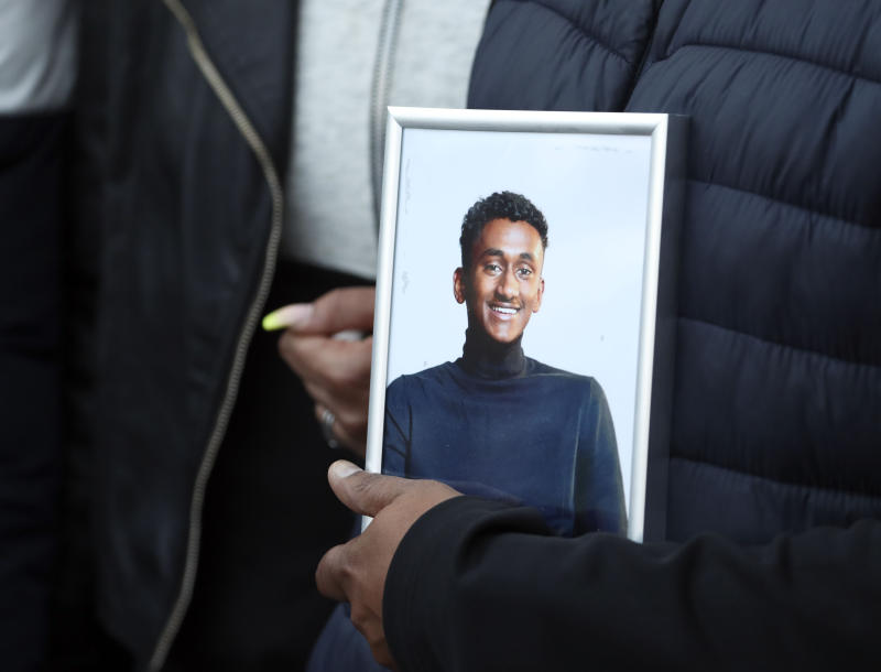Chandima Daniel, father of Tashan Daniel, who was stabbed at Hillingdon station whilst on his way to an Arsenal game on Tuesday, holds a photograph of him at a vigil held outside the underground station in London.