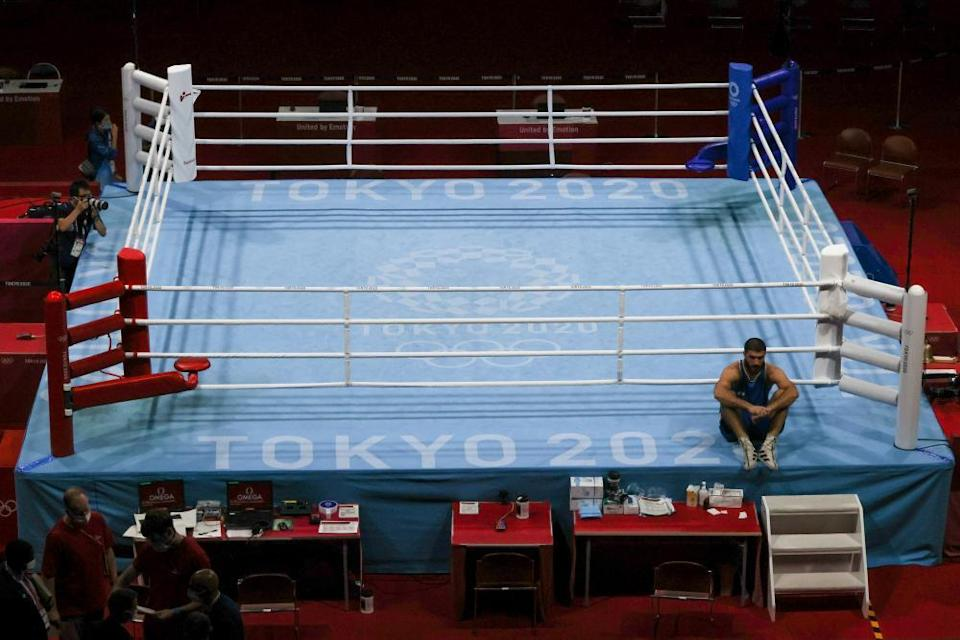 Mourad Aliev of France sits outside the ring in protest after the referee stopped his fight.