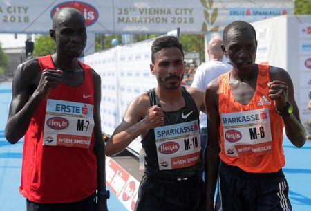 Samwel Maswai of Kenya, Salaheddine Bounasser of Morocco and Ishmael Bushendich of Kenya pose after finishing the Vienna City Marathon in Vienna, Austria, April 22, 2018. REUTERS/Heinz-Peter Bader