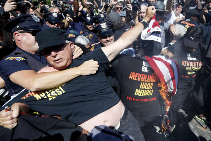 <p>A law enforcement officer clashes with protester who is holding a burning American flag, July 20, 2016, in Cleveland, during the third day of the Republican convention. (Photo: John Minchillo/AP)</p>