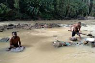 The arduous job of gold panning carries the risk of catching skin infections from wading through waters chock full of waste from the nearby mine