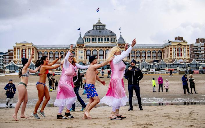 Some costumed people gather at the beach in Scheveningen, The Netherlands, on New Year's Day. The traditional New Year's Dive has been cancelled due to the coronavirus pandemic - Shutterstock