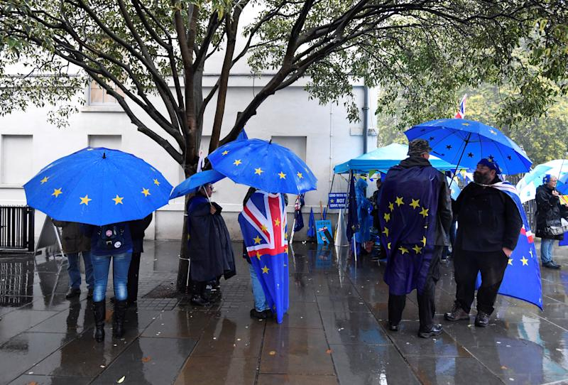 Anti-brexit and pro-EU protesters shelter from the rain outside the Houses of Parliament in London, Britain, October 24, 2019. REUTERS/Toby Melville