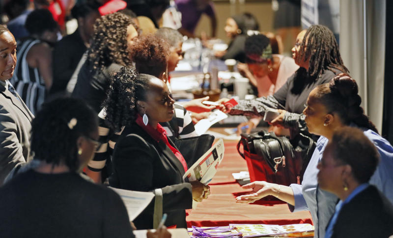 FILE - In this Aug. 14, 2019, file photo company representatives from Verizon, Goodwill, Kaiser Permanente and UPS, right, talk with potential applicants during a job and resource fair in Atlanta. On Friday, Sept. 6, the U.S. government issues the August jobs report. (Bob Andres/Atlanta Journal-Constitution via AP, File)