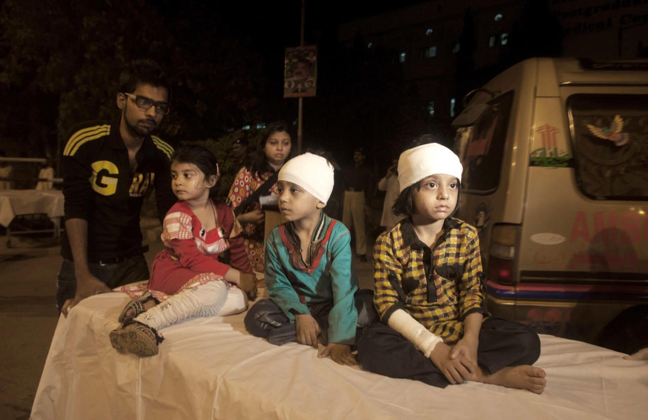 Pakistani children, who were slightly injured in a bomb blast, are brought to a hospital in Karachi, Pakistan, Sunday, March 3, 2013. Pakistani officials say a bomb blast has killed dozens of people in a neighborhood dominated by Shiite Muslims in the southern city of Karachi. (AP Photo/Shakil Adil)