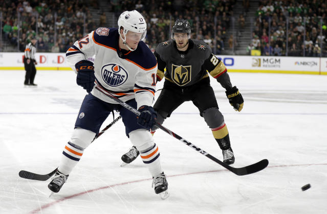 Edmonton Oilers center Colby Cave (12) takes a shot as Vegas Golden Knights defenseman Shea Theodore defends during the third period of an NHL hockey game Sunday, March 17, 2019, in Las Vegas. The Golden Knights won, 6-3. (AP Photo/Isaac Brekken)