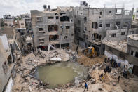 A crater full of water and sewage remains where the home of Ramez al-Masri was destroyed by an air-strike prior to a cease-fire reached after an 11-day war between Gaza's Hamas rulers and Israel, Sunday, May 23, 2021, in Beit Hanoun, the northern Gaza Strip. (AP Photo/John Minchillo)