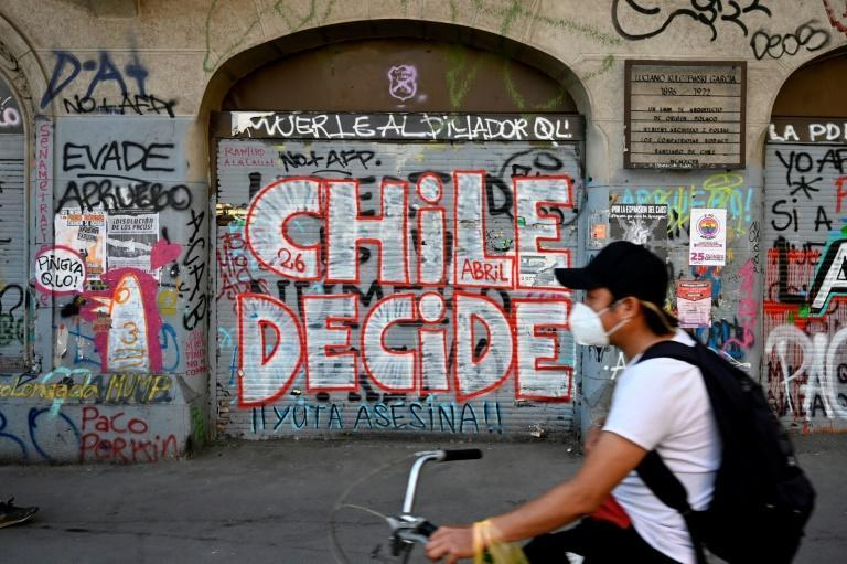"""A man rides a bicycle past a wall a graffiti reading """"Chile decides"""" in Santiago, on October 23, 2020, two days ahead of a referendum"""