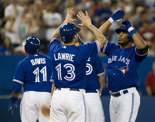 Toronto Blue Jays' Edwin Encarnacion, right, celebrates his three-run home run with teammates Brett Lawrie (13) and Rajai Davis during the fourth inning of a baseball game against the Oakland Athletics in Toronto Thursday, July 26, 2012. (AP Photo/The Canadian Press, Aaron Vincent Elkaim)