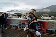 A guide speaks to the media during a government-organised media tour in the town of Lunang in Tibet
