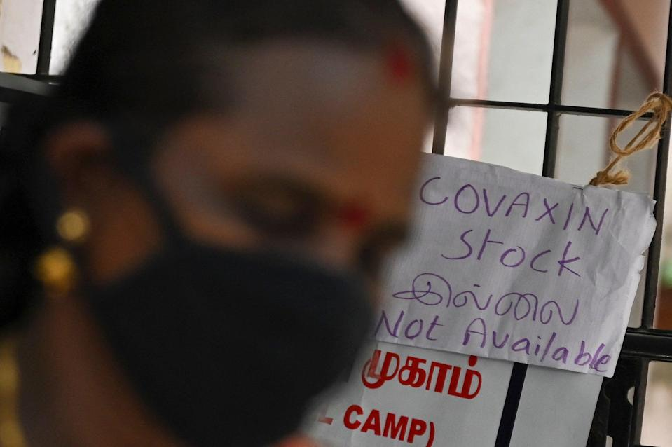 <p>A woman walks past a notice announcing the unavailability of Covid-19 vaccine doses due to stock shortages</p> (AFP via Getty Images)