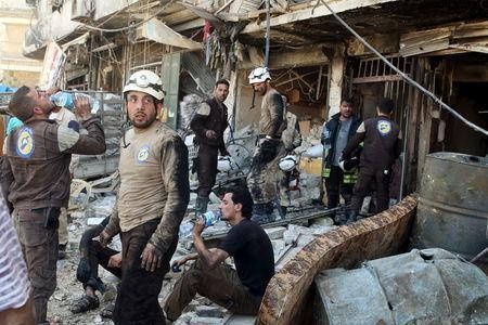 Civil defense members rest amid rubble of damaged buildings after an airstrike on the rebel-held Tariq al-Bab neighborhood of Aleppo, Syria. REUTERS/Abdalrhman Ismail