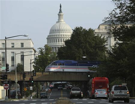 Light traffic and a Virginia Railway Express commuter train pass by the U.S. Capitol during day three of the U.S. government shutdown in Washington October 3, 2013. REUTERS/Gary Cameron