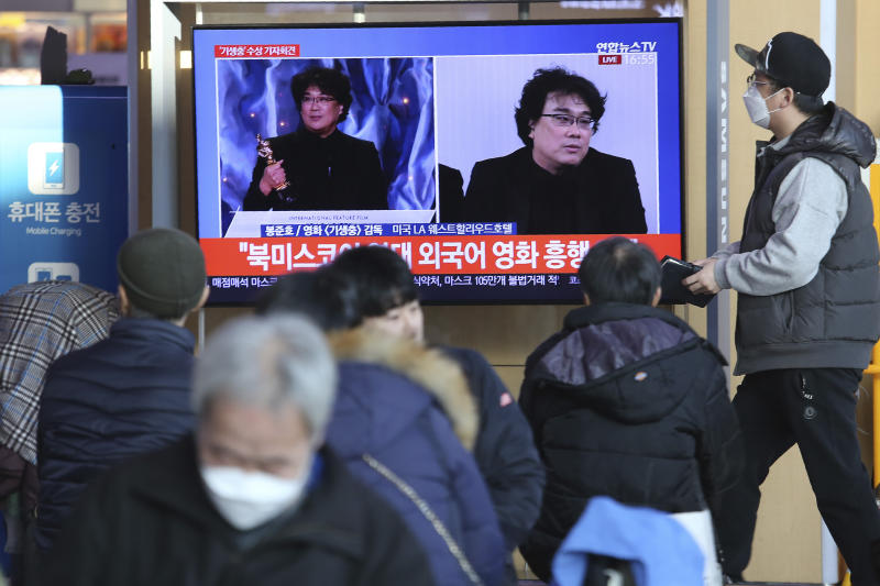 "People watch a TV screen showing images of South Korean director Bong Joon Ho during a news program at the Seoul Railway Station in Seoul, South Korea, Monday, Feb. 10, 2020. In a milestone win that instantly expanded the Oscars' horizons, Bong's masterfully devious class satire ""Parasite"" became the first non-English language film to win best picture in the 92-year history of the Academy Awards. The signs read: ""Foreign language movie."" (AP Photo/Ahn Young-joon)"