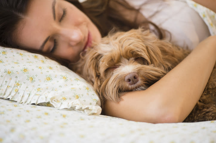 A woman cuddles her dog in bed.