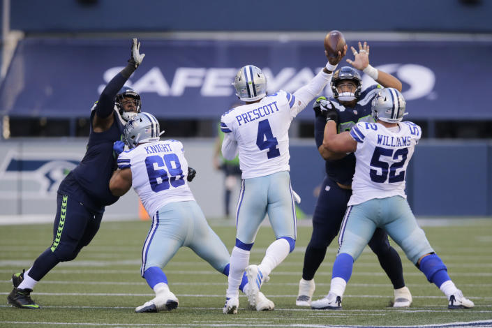 Dallas Cowboys quarterback Dak Prescott (4) passes under pressure to wide receiver Michael Gallup for a touchdown during the second half of an NFL football game, Sunday, Sept. 27, 2020, in Seattle. (AP Photo/John Froschauer)
