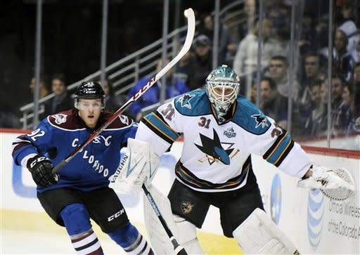 Colorado Avalanche left wing Gabriel Landeskog, left, of Sweden, and San Jose Sharks goalie Antti Niemi, of Finland, watch the puck in the first period of an NHL hockey game on Sunday, March 10, 2013, in Denver.  (AP Photo/Chris Schneider)