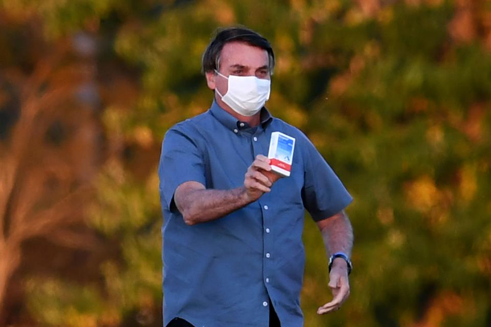 """TOPSHOT - Brazilian President Jair Bolsonaro shows a box of hydroxychloroquine to supporters outside the Alvorada Palace in Brasilia, on July 23, 2020. - In a study published in """"The New England Journal of Medicine"""", Brazilian researchers from 55 hospitals point out that hydroxychloroquine was not effective in treating COVID-19 in patients with mild and moderate cases. The study shows that, after 15 days of treatment, similar percentages of patients, who took hydroxychloroquine or not, were already at home """"without respiratory limitations"""". The percentage of deaths was the same in all groups: 3%. (Photo by EVARISTO SA / AFP) (Photo by EVARISTO SA/AFP via Getty Images)"""