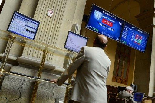 A trader looks an index billboard at Madrid's stock exchange. A full-blown bailout for Spain, the fourth-largest economy in the eurozone, would dwarf the rescues of Ireland, Greece and Portugal and strain the resources of the EU bloc to the limit