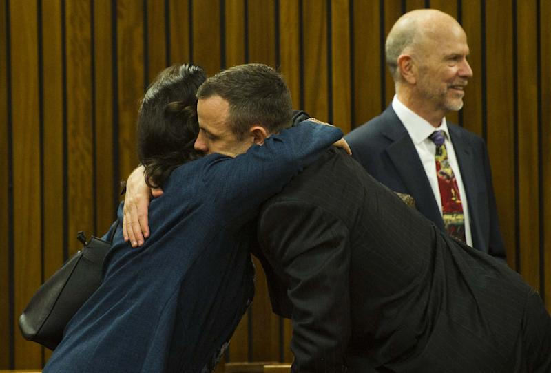 Oscar Pistorius, center, gets a hug from a relative, left, with uncle Arnold Pistorius, right, in court in Pretoria, South Africa, Thursday, April 17, 2014. Pistorius is charged with the murder of his girlfriend, Reeva Steenkamp, on Valentines Day in 2013. (AP Photo/Alet Pretorius, Pool)