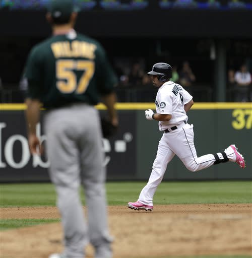 Seattle Mariners' Kendrys Morales, right, circles the bases on a home run as Oakland Athletics starting pitcher Tommy Milone watches in the first inning of a baseball game on Sunday, May 12, 2013, in Seattle. (AP Photo/Elaine Thompson)
