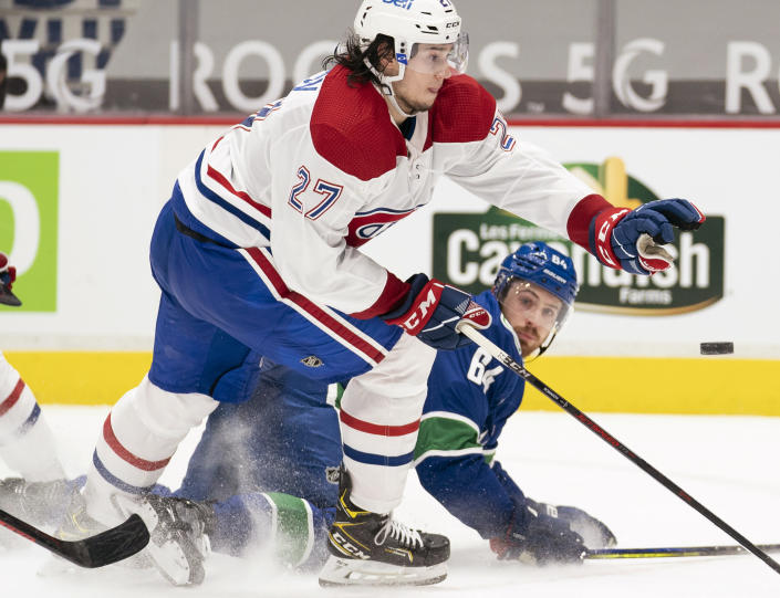Vancouver Canucks centre Tyler Motte (64) competes for control of the puck against Montreal Canadiens defenseman Alexander Romanov (27) during the second period of an NHL hockey game Wednesday, Jan. 20, 2021, in Vancouver, British Columbia. (Jonathan Hayward/The Canadian Press via AP)