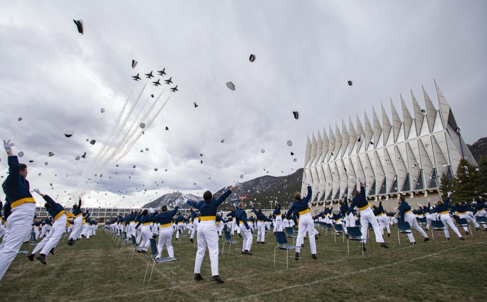 The class of 2020 toss their caps into the air as the Thunderbirds fly over Saturday, April 18, 2020, at the conclusion of the Air Force Academy graduation in Colorado Springs, Colo. Nearly 1,000 cadets graduated in a scaled-down ceremony due to the coronavirus pandemic. Saturday's commencement was attended by Vice President Mike Pence and capped a difficult final semester in which the cadets attended virtual classes and ate their meals alone in dorm rooms. (Christian Murdock/The Gazette via AP)