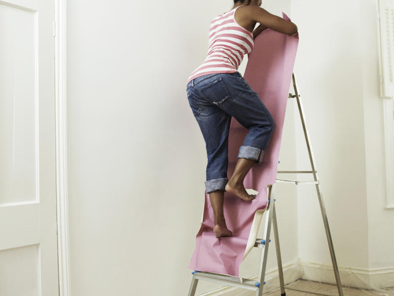 Woman treading on and tearing wallpaper whilst walking up step ladder