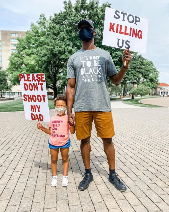 """<i>Breezy Rose of Kansas posted this photo of her husband holding a sign that says """"Stop killing us"""" and her daughter holding a sign that says """"Please don't shoot my dad"""" on Instagram. In the caption, Breezy wrote: """"When I tell you I cried after snapping this picture at a rally for George Floyd today, I sobbed. This is our reality. This is reality for every black person in our country. Today I wept for George Floyd, for Breonna Taylor, for Ahmaud Arbery, for Eric Garner, for Sandra Bland, for Tamir Rice and for so many others. Today I wept for my husband having to teach this to our daughter. And today I wept for our daughter, who has to grow up with this fear. Today, we wept. But tomorrow, we fight."""" </i>"""