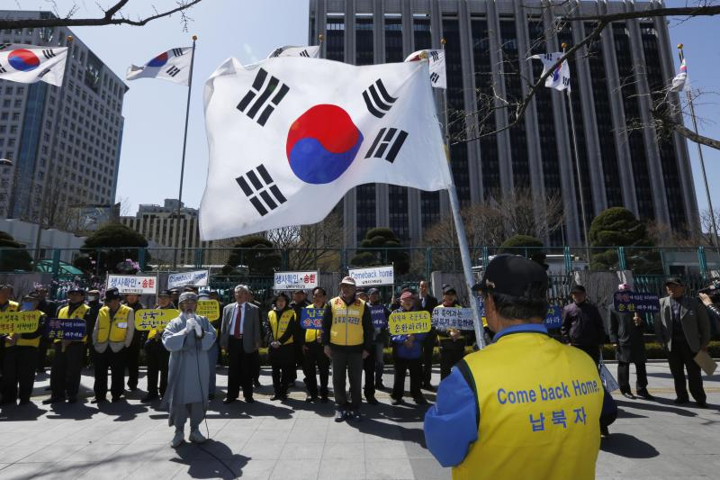South Korean members of the Abductees Family Association with their national flags hold an anti-North Korea rally in Seoul, South Korea, Sunday, April 14, 2013. As the world watches to see what North Korea's next move will be in a high-stakes game of brinksmanship with the United States, residents of its capital aren't hunkering down in bunkers and preparing for the worst. Instead, they are out on the streets en masse getting ready for the birthday of national founder Kim Il Sung - the biggest holiday of the year. (AP Photo/Kin Cheung)