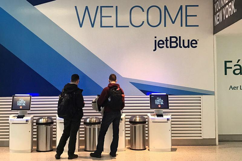 Travelers check-in at a JetBlue Airways kiosk at John F. Kennedy Airport in the Queens borough of New York