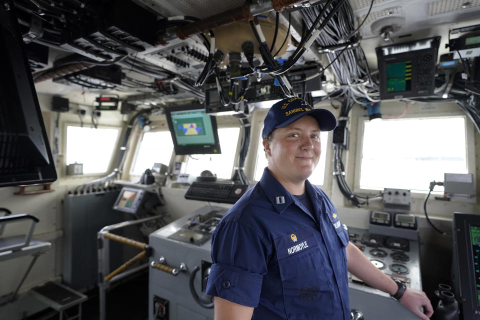"""U.S. Coast Guard Lt. Kelli Normoyle, Commanding Officer of the Coast Guard Cutter Sanibel, stands for a photograph on the bridge of the vessel, Thursday, Sept. 16, 2021, at a shipyard in North Kingstown, R.I. Normoyle was one of two cadets who formally started the process to create the CGA Spectrum Diversity Council just a few months after the law known as """"don't ask, don't tell"""" was repealed on Sept. 20, 2011. (AP Photo/Steven Senne)"""