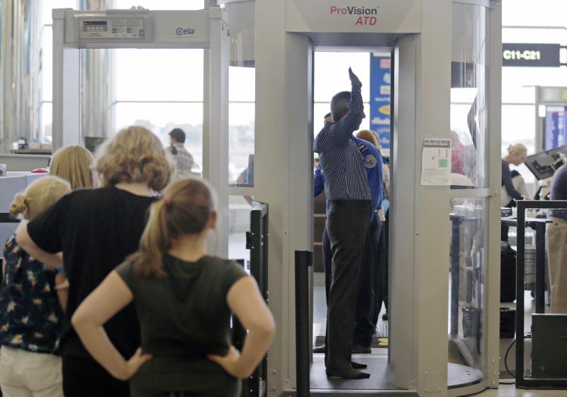FILE - In this Wednesday, Oct. 24, 2012 file photo, passengers are scanned at a security checkpoint at Logan Airport in Boston using a millimeter wave body scanner. Frustration is growing among small airport managers outraged that the newer millimeter wave scanners, that produces a cartoon-like outline of the body, are being hauled away and sent to bigger facilities that haven't yet upgraded older machines criticized for showing too much anatomy. (AP Photo/Charles Krupa, File)
