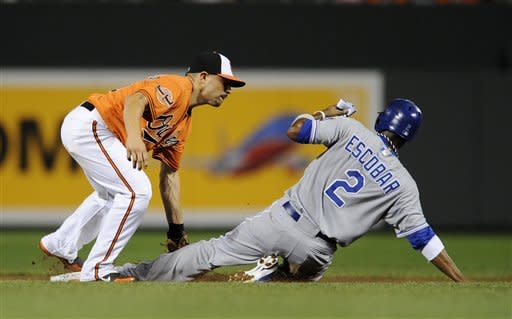 Kansas City Royals' Alcides Escobar (2) is caught stealing by Baltimore Orioles second baseman Omar Quintanilla during the first inning of a baseball game, Saturday, Aug. 11, 2012, in Baltimore. (AP Photo/Nick Wass)