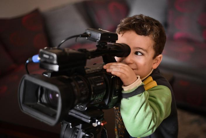 Hazem, one of the children of al-Jazeera's Egyptian producer Baher Mohamed, plays with a video camera during an interview of his mother by AFP journalists on February 5, 2015 in the capital Cairo (AFP Photo/Mohamed el-Shahed)
