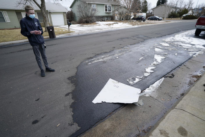 A man looks over debris that fell off a plane as it shed parts over a neighborhood in Broomfield, Colo., Saturday, Feb. 20, 2021. The plane was making an emergency landing at nearby Denver International Airport. (AP Photo/David Zalubowski)