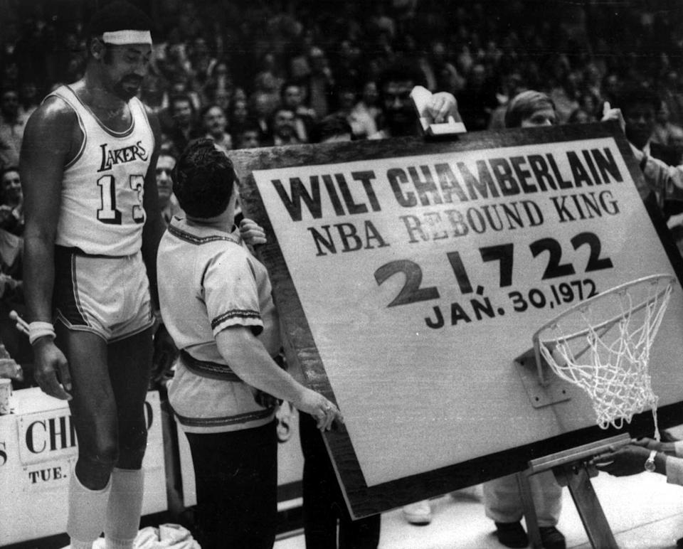 Los Angeles Lakers' Wilt Chamberlain, left, stands beside a backboard and hoop trophy that was presented to him after he became the all-time leading rebounder in NBA history, in Los Angeles, Jan. 31, 1972.  (AP Photo)