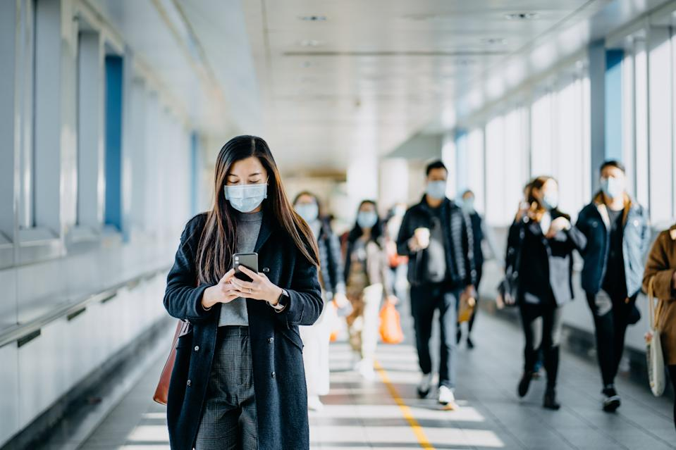Asian woman with protective face mask using smartphone while commuting in the urban bridge in city against crowd of people