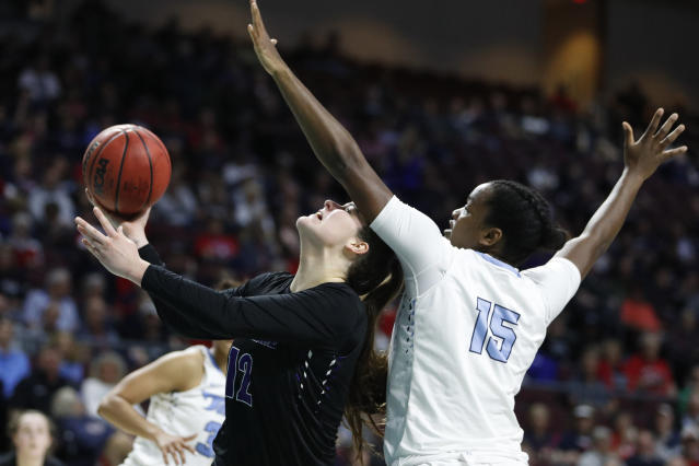 Portland's Alex Fowler (12) shoots around San Diego's Leticia Soares (15) during the first half of an NCAA college basketball game in the final of the West Coast Conference women's tournament Tuesday, March 10, 2020, in Las Vegas. (AP Photo/John Locher)