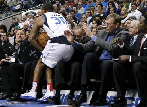 Dallas Mavericks' Dahntay Jones (30) chases a ball out of bounds and falls into the lap of Minnesota Timberwolves head coach Rick Adelman as members of the coaching staff watch during the first half of an NBA basketball game, Monday, Nov. 12, 2012, in Dallas. (AP Photo/Tony Gutierrez)