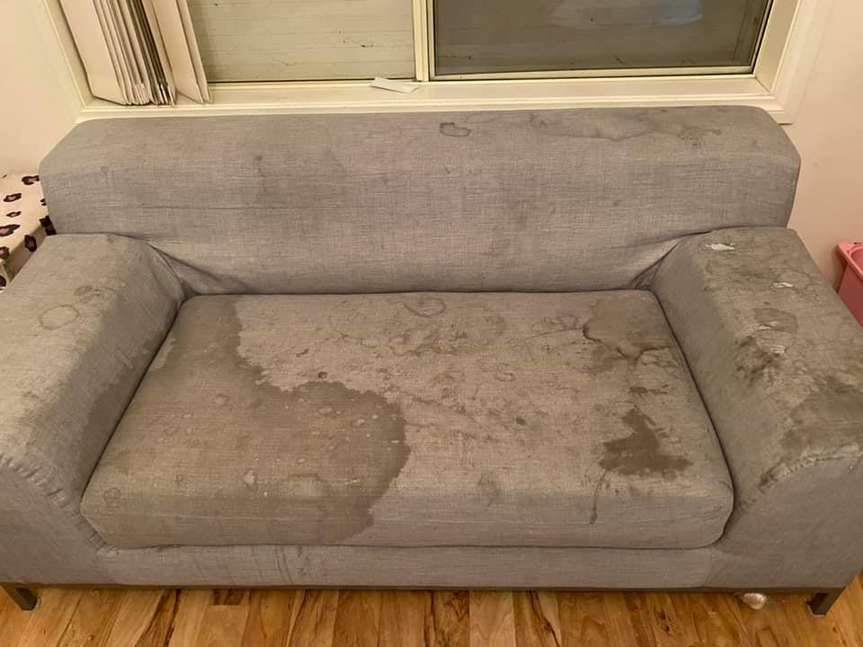 A very dirty and stained couch inside a children's playroom