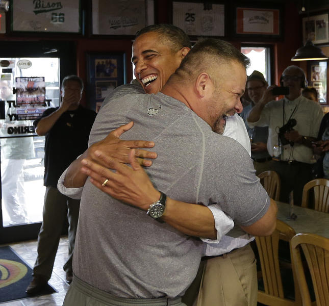 """In this photo taken Sept. 9, 2012, President Barack Obama, right, is hugged by Scott Van Duzer, owner of Big Apple Pizza and Pasta Italian Restaurant in Ft. Pierce, Fla. Obama's handlers let the muscular restaurant owner hoist the president off the ground in a big bear hug during a drop-by visit. """"Look at these guns!"""" Obama enthused about the man's biceps. Every day, the ground troops of Team Obama and Team Romney set out in pursuit of a common goal: winning the day. Everyone poses for the camera. (AP Photo/Pablo Martinez Monsivais)"""