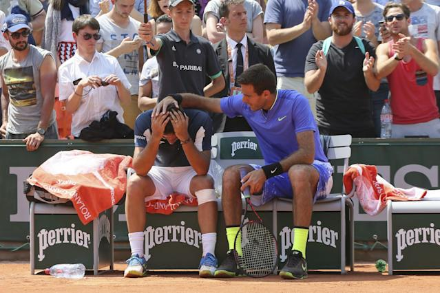"Nicolas Almagro, left, is comforted by <a class=""link rapid-noclick-resp"" href=""/olympics/rio-2016/a/1100647/"" data-ylk=""slk:Juan Martin del Potro"">Juan Martin del Potro</a> after he collapsed with a left knee injury in his second round match against at the French Open. (AP Images)"