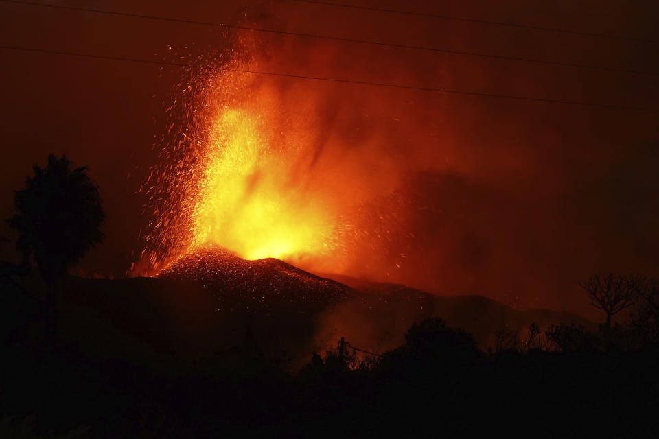 Lava erupts from a volcano near El Paso on the island of La Palma in the Canaries, Spain, Monday Sept. 20, 2021. Giant rivers of lava are tumbling slowly but relentlessly toward the sea after a volcano erupted on a Spanish island off northwest Africa. The lava is destroying everything in its path but prompt evacuations helped avoid casualties after Sunday's eruption. (Europa Press via AP)