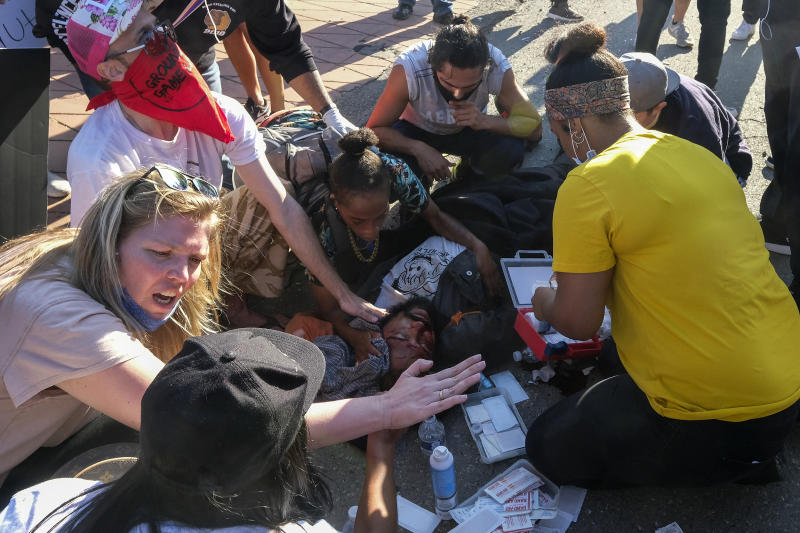 Demonstrators help a man who was sitting on a police car and injured by falling onto the ground during a protest to demand justice for George Floyd in downtown Los Angeles on May 27, 2020. (Ringo H.W. Chiu / AP)