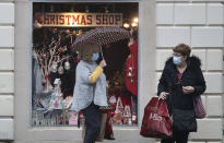 People wearing face coverings outside a Christmas Shop in Stirling, Scotland, Friday Nov. 20, 2020. This shop will close later Friday along with other non-essential shops, bars, restaurants, hairdressers and visitor attractions whilst schools remain open, due to the latest government restrictions imposed to slow the spread of coronavirus. (Andrew Milligan/PA via AP)