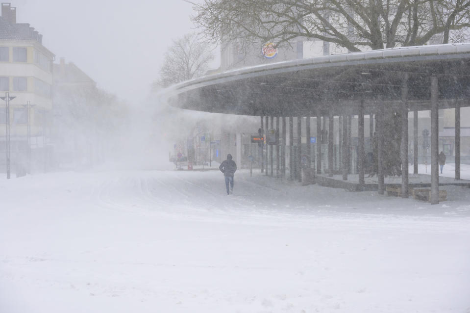 Snow blows from the roof of the bus station at the central station in Osnabrueck, Germany, Sunday, Feb. 7, 2021. Bus services were suspended on Sunday morning. (Jonas Walzberg/dpa via AP)