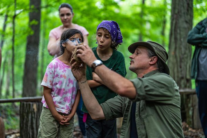 Shane Hobel puts an ember into cambium to start a fire while Sahira Pawria-Sanchez and Ara Bella Pajoohi blow on the ember. (Michael Rubenstein / for NBC News)