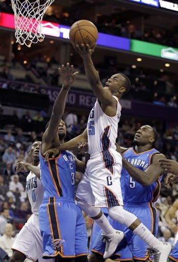 Charlotte Bobcats' Kemba Walker (15) gets to the basket past Oklahoma City Thunder's Kevin Durant (35) and Kendrick Perkins (5) during the first half of an NBA basketball game in Charlotte, N.C., Friday, March 8, 2013. (AP Photo/Bob Leverone)